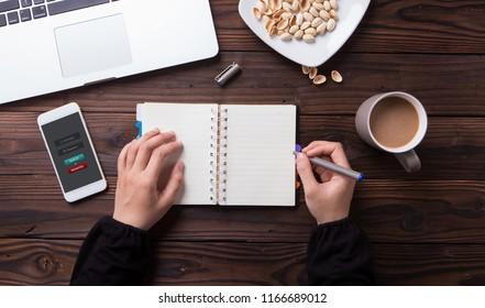 Woman sign in membership username password concept on smartphone and write something on notebook with wooden desk background