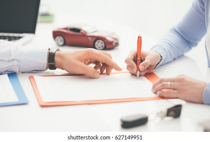 Woman signing a car insurance policy, the agent is pointing at the document