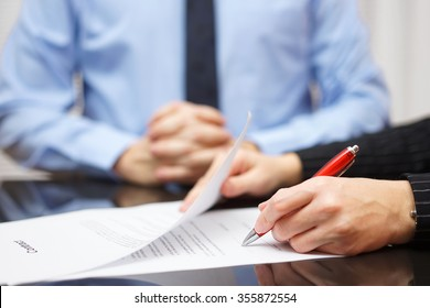 woman is signing contract with business man in background