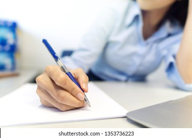 Woman signing document, close up on female hand holding pen and paper on table.