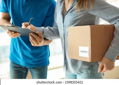 Woman signing documents to confirm receiving of order from delivery company