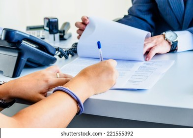A woman is signing a legal document
