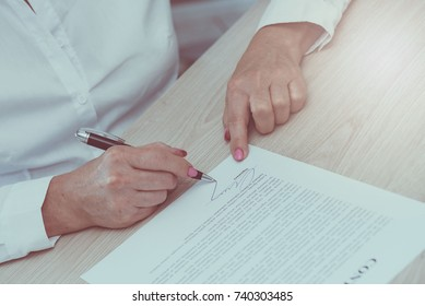 Woman signing a legal document