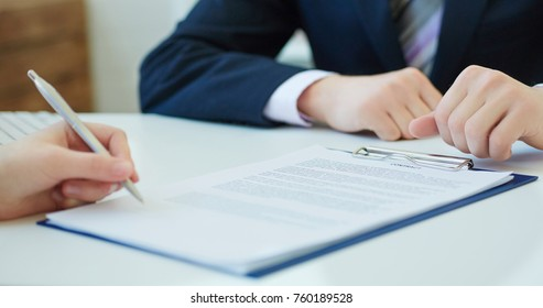 Woman signing a loan agreement.