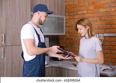Woman signing receipt for plumber service at home