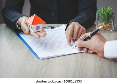 A woman signs a contract to purchase a home with a real estate agent. Model house in hand.