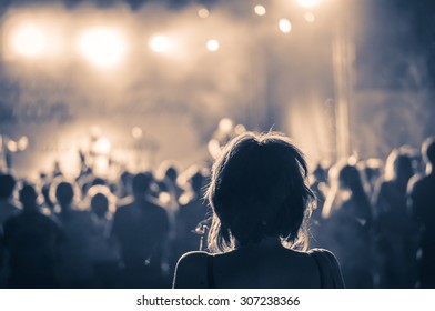 woman silhouette in a crowd at a concert in a vintage light, noise added