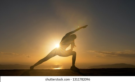 Woman silhouette doing yoga fitness exersice at sea beach in sunrise.