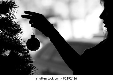Woman silhouette dresses up Christmas tree (black white)