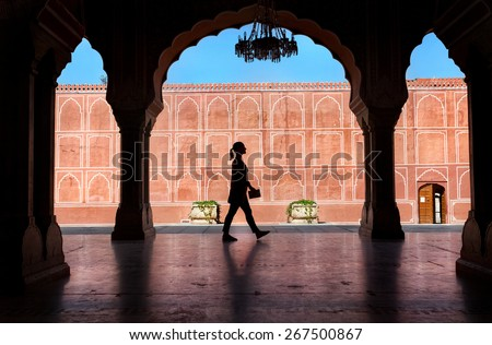 Woman silhouette with guidebook walking in the City Palace museum, Jaipur, Rajasthan, India