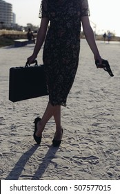 Woman silhouette with gun and briefcase on summer sunny sky outdoors background. Ready for meeting
