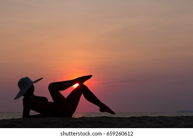 Woman silhouette with hat lying on sunset sea background, back lit