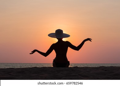 Woman silhouette with hat sitting on sunset sea background, back lit
