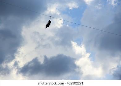 Woman silhouette high-speed sliding via zip-line against cloudy sky.