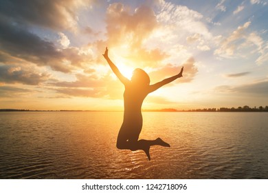 Woman silhouette jumping on sunset sea background. Summer vacation concept