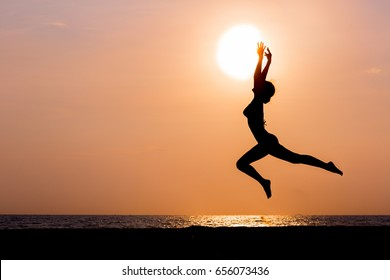 Woman silhouette jumping on sunset sea background, back lit