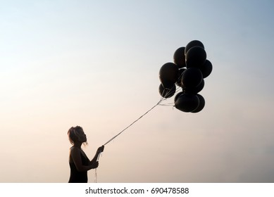 Woman in silhouette looking at black balloons about to let go set against a stark clean background and sky at sunset