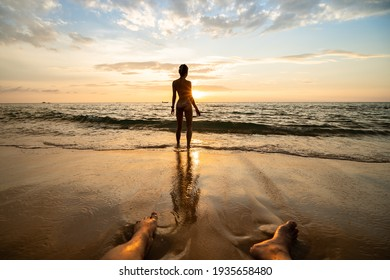 Woman silhouette on the beach at sunset with man legs.