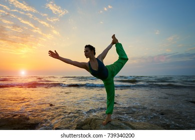 Woman silhouette on sunset sky background young active girl sit in yoga pose on beach rock. Yoga professional performing pose and handstand peaceful healthy young girl doing power pose