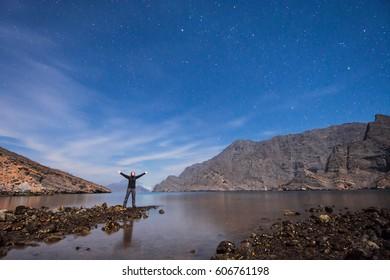 Woman silhouette over blue night sky, Musandam peninsula, Oman, Arabia