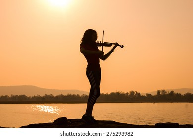 Woman silhouette playing violin in sunrise sky background.