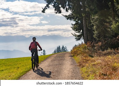 Woman as silhouette riding her electric mountain bike in the Allgaeu alps near Oberstaufen with awesome view into the Bregenz Wald Mountains, Vorarlberg Switzerland - Shutterstock ID 1857654622