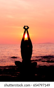 Woman silhouette sitting in lotus position on sunset sea background back lit