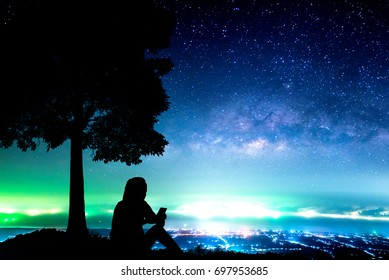 Woman in silhouette sitting near big tree. Night sky with milky way stars and city lights at background.
