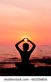Woman silhouette sitting in yoga pose on sunset sea background back lit