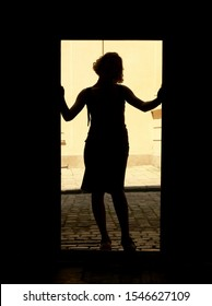 Woman silhouette standing in the bright doorway