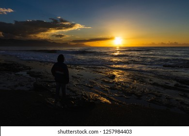 Woman silhouette standing on a beach watching the sunrise