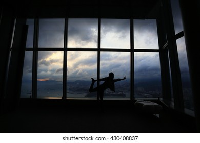 . Woman silhouette in the window sunset background.