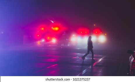 A woman silhouetted against the lights of emergency vehicles