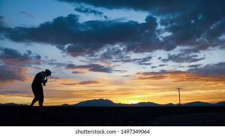 A woman silhouetted against a sunset photographing railroad tracks.