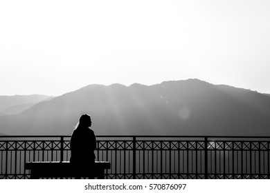 Woman silhouetted By The Mountains