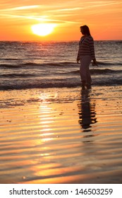 Woman Silhouetted by the Setting Sun Takes a Stroll on the Beach