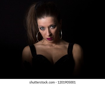 A woman with silver earrings, red lipstick big blue green eyes and decolletage is looking straight to camera