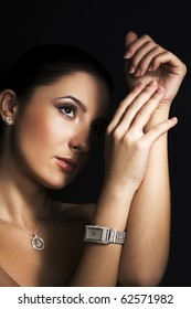 Woman with silver jewelry on dark background
