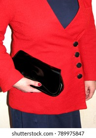 A woman in a simple red jacket with a black clutch
