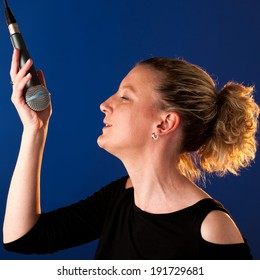 Woman singer on bluue background with microphone singing
