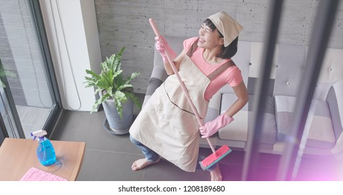 Woman singing and dancing while doing housework at home