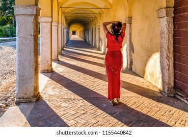 Woman with a sinuous body she holds her hair in front of a long porch looking to vanishing point