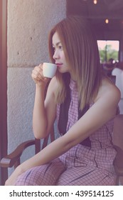 Woman sipping coffee in comfort. , Bright pink