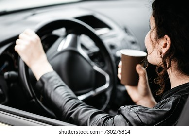 Woman sipping a coffee while driving a car.