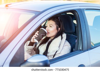 Woman sipping coffee while driving car.