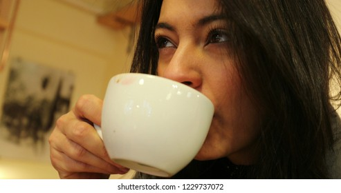 Woman sipping cup of coffee. Woman sips cup of tea