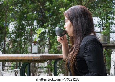 woman is sipping hot coffee at coffee time at park or garden and relax atmosphere
