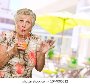 Woman Sipping Juice Through Straw, Outdoors