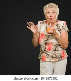 Woman Sipping Juice Through Straw Isolated On Black Background