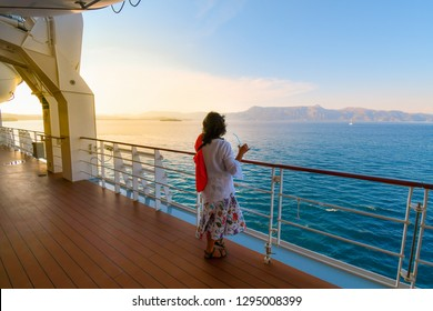 A woman sips a drink on the deck of a cruise ship as the sun sets and the ship passes islands on the Aegean Sea